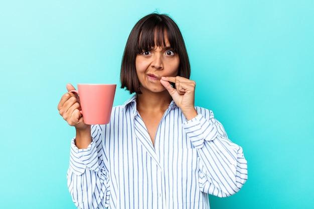 Jonge gemengde rasvrouw die een roze mok houdt die op blauwe achtergrond met vingers op lippen wordt geïsoleerd die een geheim houden.