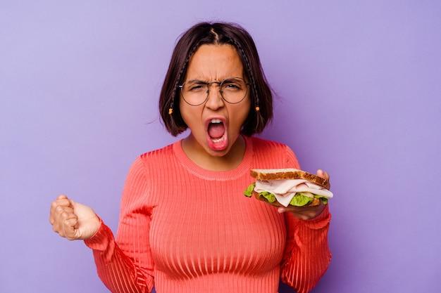 Jonge gemengde rasvrouw die een sandwich houden die op purpere achtergrond wordt geïsoleerd die zeer boos en agressief gillen.
