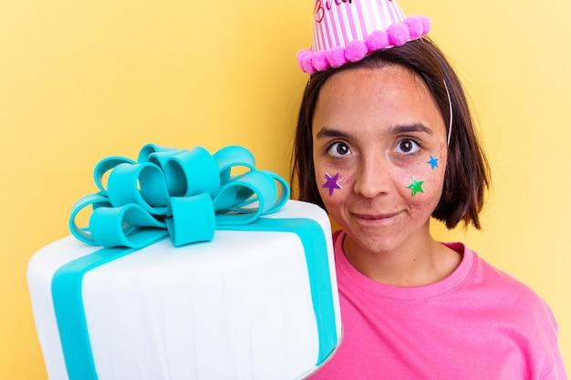 Jonge gemengde rasvrouw die een verjaardagstaart houdt die op gele achtergrond wordt geïsoleerd