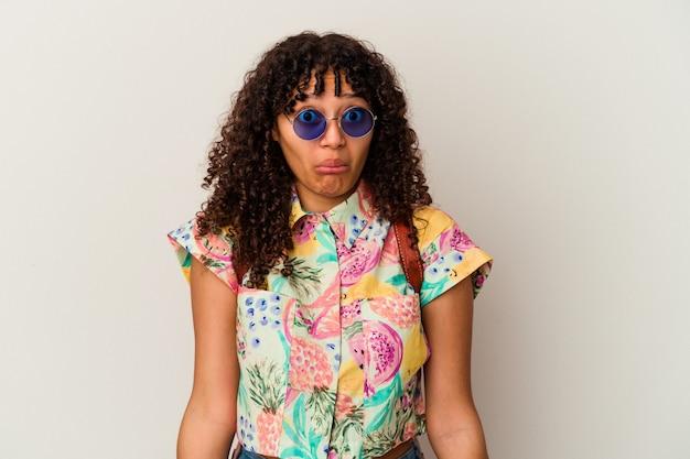 Jonge gemengde rasvrouw die een zonnebril draagt die een geïsoleerde vakantie neemt, haalt de schouders op en opent verwarde ogen.