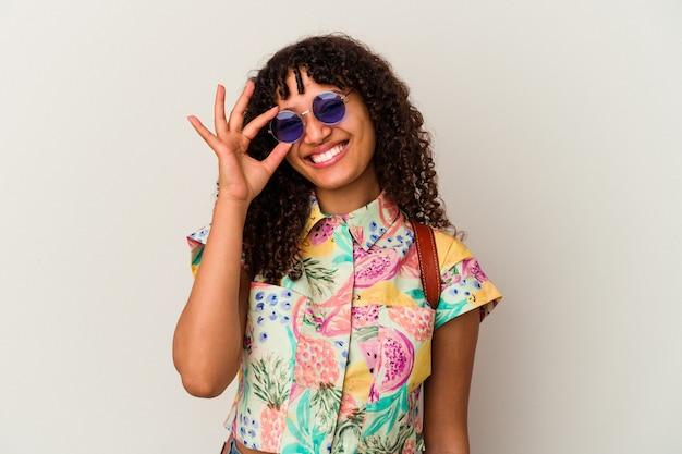 Jonge gemengde rasvrouw die een zonnebril draagt die een geïsoleerde vakantie neemt opgewonden houdt ok gebaar op oog.