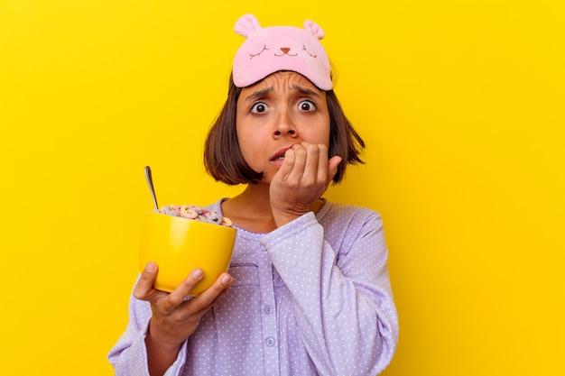 Jonge gemengde rasvrouw die granen eet die een pijama dragen die op gele achtergrond wordt geïsoleerd die vingernagels bijt, zenuwachtig en zeer angstig.