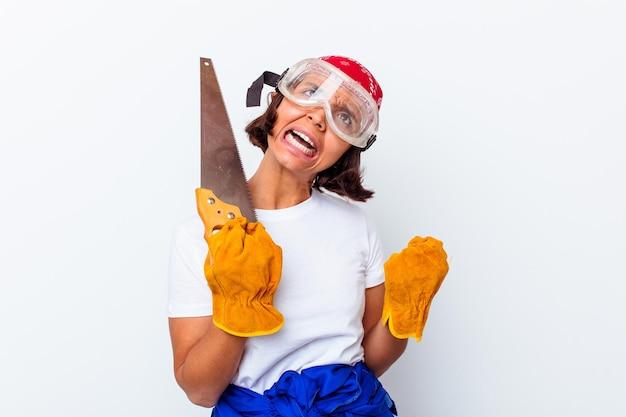 Jonge gemengde rasvrouw die haar huis herstelt met een zaag die op witte muur wordt geïsoleerd