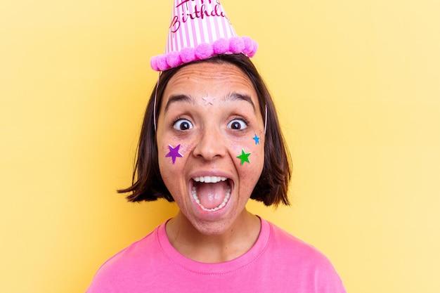Jonge gemengde rasvrouw die haar verjaardag viert, gezichtsclose-up.