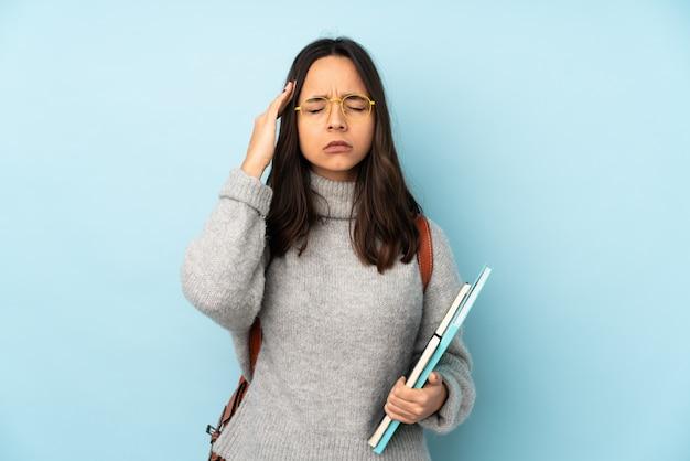Jonge gemengde rasvrouw die naar school gaan die op blauw met hoofdpijn wordt geïsoleerd