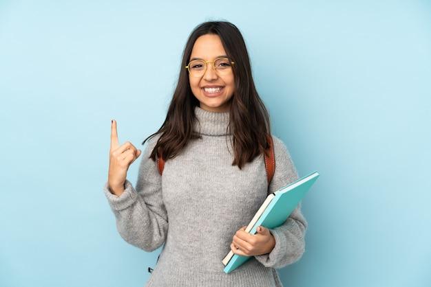 Jonge gemengde rasvrouw die naar school gaat die op blauwe achtergrond wordt geïsoleerd die een geweldig idee benadrukt