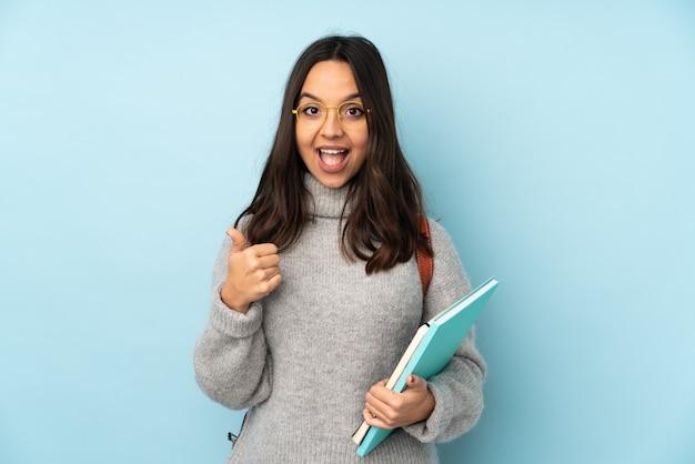 Jonge gemengde rasvrouw die naar school gaat die op blauwe achtergrond wordt geïsoleerd die ok teken en duim omhoog gebaar toont