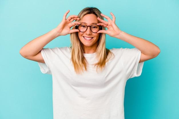 Jonge gemengde rasvrouw die op blauw wordt geïsoleerd dat ogen geopend houdt om een succeskans te vinden.