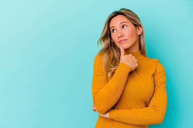 Jonge gemengde rasvrouw die op blauw wordt geïsoleerd dat zijwaarts met twijfelachtige en sceptische uitdrukking kijkt.