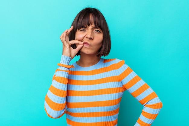 Jonge gemengde rasvrouw die op blauwe achtergrond met vingers op lippen wordt geïsoleerd die een geheim houden.