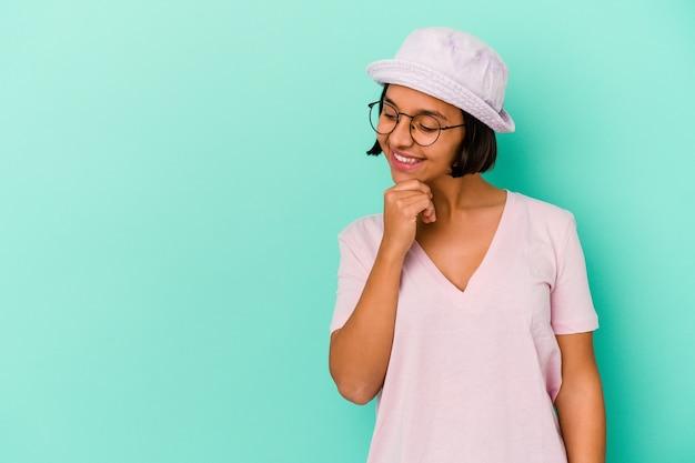 Jonge gemengde rasvrouw die op blauwe achtergrond wordt geïsoleerd die achterkant van het hoofd raakt, denkt en een keus maakt.