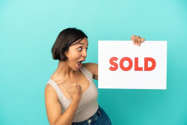 Jonge gemengde rasvrouw die op blauwe achtergrond wordt geïsoleerd die een aanplakbiljet met tekst verkocht houdt en een overwinning viert