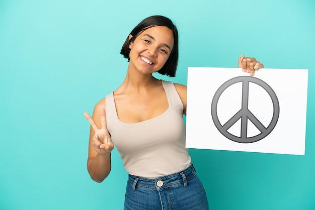 Jonge gemengde rasvrouw die op blauwe achtergrond wordt geïsoleerd die een aanplakbiljet met vredessymbool houdt en een overwinning viert