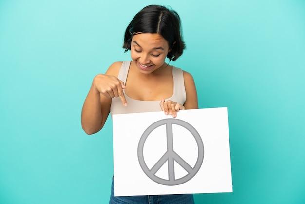 Jonge gemengde rasvrouw die op blauwe achtergrond wordt geïsoleerd die een aanplakbiljet met vredessymbool houdt en het richt