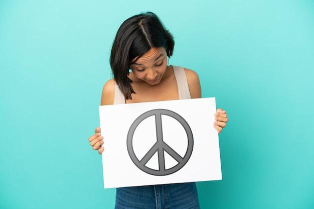 Jonge gemengde rasvrouw die op blauwe achtergrond wordt geïsoleerd die een aanplakbiljet met vredessymbool houdt