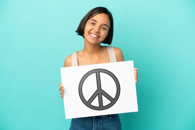 Jonge gemengde rasvrouw die op blauwe achtergrond wordt geïsoleerd die een aanplakbiljet met vredessymbool met gelukkige uitdrukking houdt