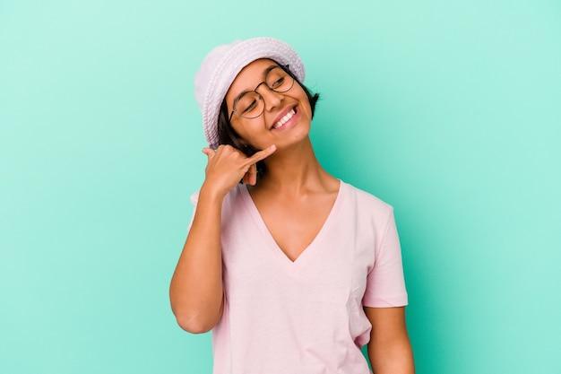 Jonge gemengde rasvrouw die op blauwe achtergrond wordt geïsoleerd die een mobiel telefoongesprekgebaar met vingers toont.