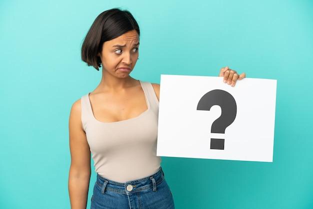 Jonge gemengde rasvrouw die op blauwe achtergrond wordt geïsoleerd die een plakkaat met vraagtekensymbool houdt