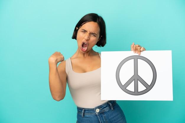 Jonge gemengde rasvrouw die op blauwe achtergrond wordt geïsoleerd die een plakkaat met vredessymbool houdt en sterk gebaar doet