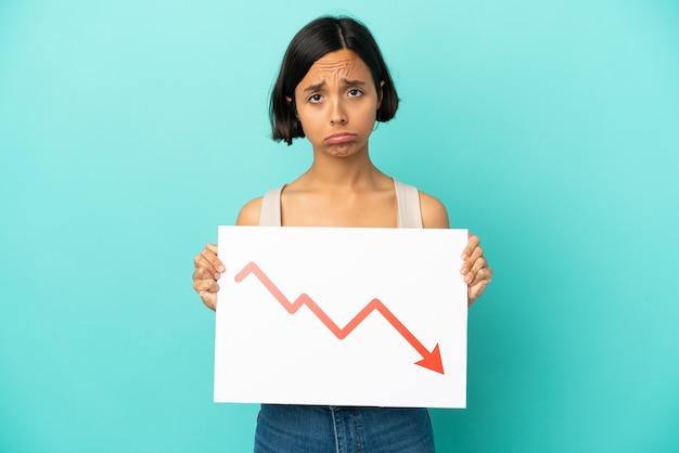 Jonge gemengde rasvrouw die op blauwe achtergrond wordt geïsoleerd die een teken met een dalend statistiekenpijlsymbool houdt met droevige uitdrukking