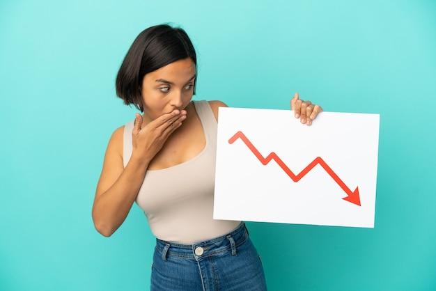 Jonge gemengde rasvrouw die op blauwe achtergrond wordt geïsoleerd die een teken met een dalend statistiekenpijlsymbool houdt met verbaasde uitdrukking