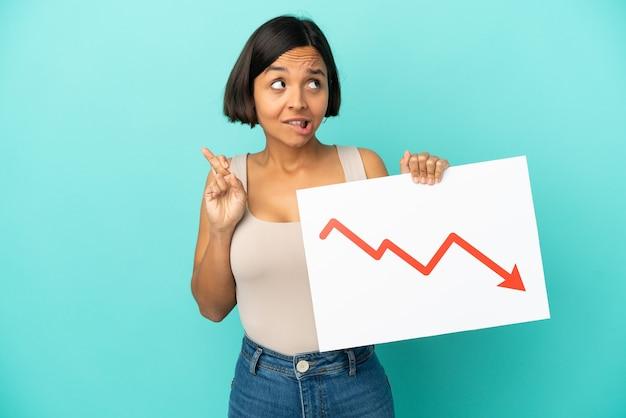 Jonge gemengde rasvrouw die op blauwe achtergrond wordt geïsoleerd die een teken met een dalend statistiekpijlsymbool houdt met het kruisen van de vingers