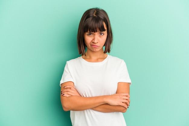Jonge gemengde rasvrouw die op blauwe achtergrond wordt geïsoleerd die ogen open houdt om een succeskans te vinden.