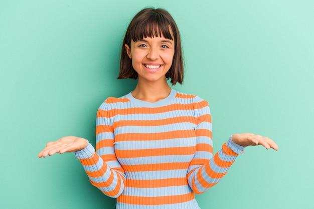 Jonge gemengde rasvrouw die op blauwe achtergrond wordt geïsoleerd die ok teken over ogen toont
