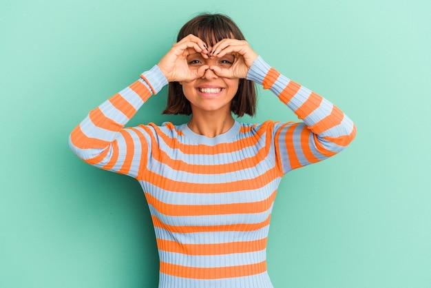 Jonge gemengde rasvrouw die op blauwe achtergrond wordt geïsoleerd die rotsgebaar met vingers toont