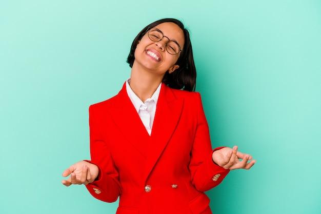 Jonge gemengde rasvrouw die op blauwe achtergrond wordt geïsoleerd ontspannen en gelukkig lachen, gestrekte nek met tanden.