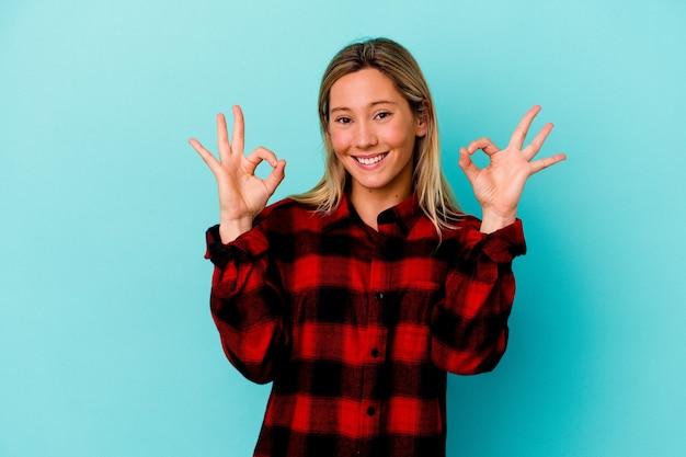 Jonge gemengde rasvrouw die op blauwe muur wordt geïsoleerd vrolijk en zelfverzekerd tonend ok gebaar.