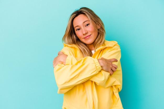 Jonge gemengde rasvrouw die op blauwe muuromhelzingen wordt geïsoleerd, zorgeloos en gelukkig glimlachen.