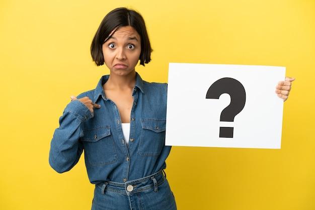 Jonge gemengde rasvrouw die op gele achtergrond wordt geïsoleerd die een aanplakbiljet met vraagtekensymbool met verbaasde uitdrukking houdt