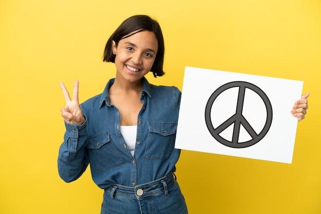 Jonge gemengde rasvrouw die op gele achtergrond wordt geïsoleerd die een aanplakbiljet met vredessymbool houdt en een overwinning viert