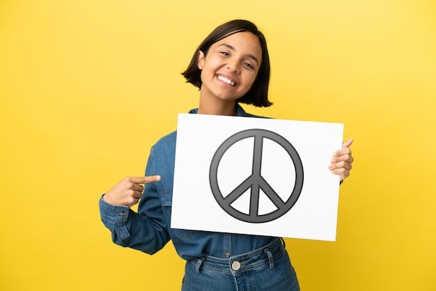 Jonge gemengde rasvrouw die op gele achtergrond wordt geïsoleerd die een aanplakbiljet met vredessymbool houdt en het richt