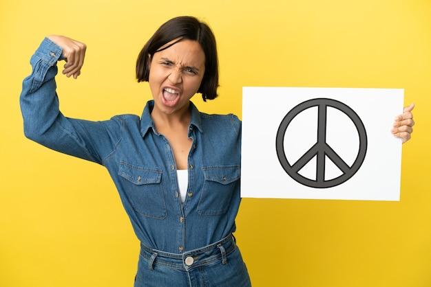 Jonge gemengde rasvrouw die op gele achtergrond wordt geïsoleerd die een aanplakbiljet met vredessymbool houdt en sterk gebaar doet