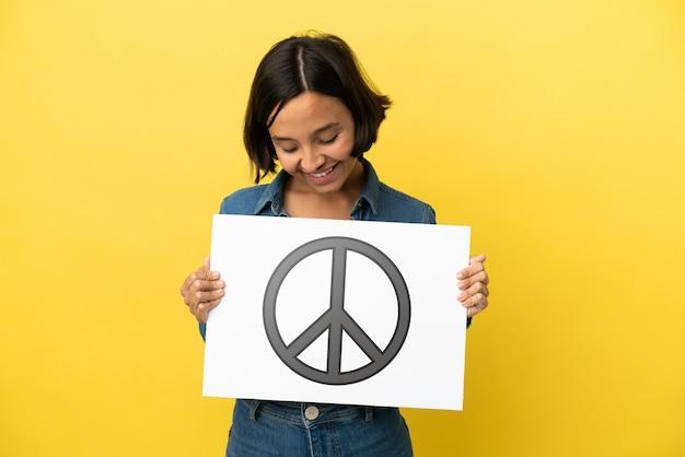 Jonge gemengde rasvrouw die op gele achtergrond wordt geïsoleerd die een aanplakbiljet met vredessymbool houdt