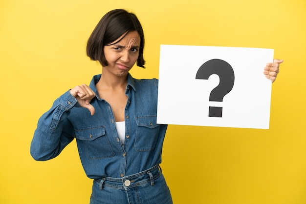 Jonge gemengde rasvrouw die op gele achtergrond wordt geïsoleerd die een plakkaat met vraagtekensymbool houdt en slecht signaal doet