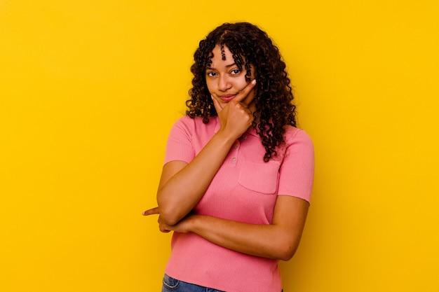 Jonge gemengde rasvrouw die op gele achtergrond wordt geïsoleerd die, een strategie plant, nadenkt over de manier van een bedrijf.