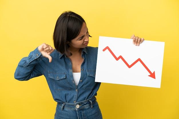 Jonge gemengde rasvrouw die op gele achtergrond wordt geïsoleerd die een teken met een dalend statistiekenpijlsymbool houdt en slecht signaal doet