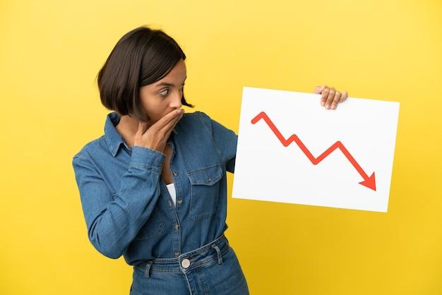 Jonge gemengde rasvrouw die op gele achtergrond wordt geïsoleerd die een teken met een dalend statistiekenpijlsymbool houdt met verbaasde uitdrukking