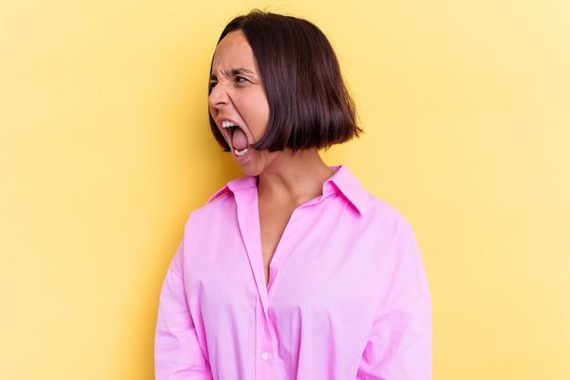 Jonge gemengde rasvrouw die op gele achtergrond wordt geïsoleerd die naar een exemplaarruimte schreeuwt