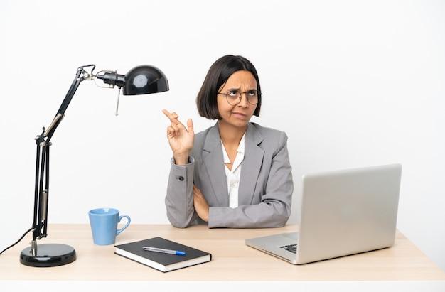 Jonge gemengde rasvrouw die op kantoor werken met vingers die kruisen en het beste wensen