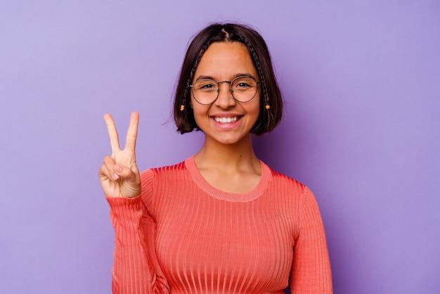 Jonge gemengde rasvrouw die op purpere muur wordt geïsoleerd die nummer twee met vingers toont.