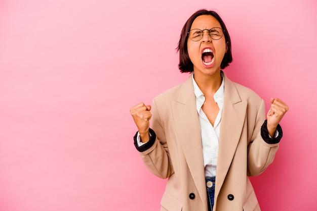 Jonge gemengde rasvrouw die op roze achtergrond wordt geïsoleerd die vuist opheft na een overwinning, winnaarconcept.