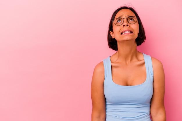 Jonge gemengde rasvrouw die op roze achtergrond wordt geïsoleerd die zeer boos, gefrustreerd woedeconcept schreeuwt.