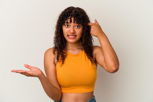 Jonge gemengde rasvrouw die op witte muur wordt geïsoleerd die en een product bij de hand toont.