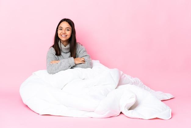 Jonge gemengde rasvrouw die pijama draagt, zittend op de vloer met gekruiste armen en vooruit kijkend