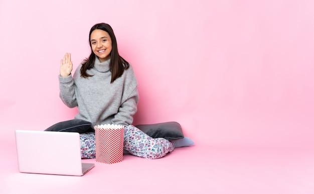 Jonge gemengde rasvrouw die popcorn eet tijdens het kijken naar een film op de laptop die met hand met gelukkige uitdrukking groet