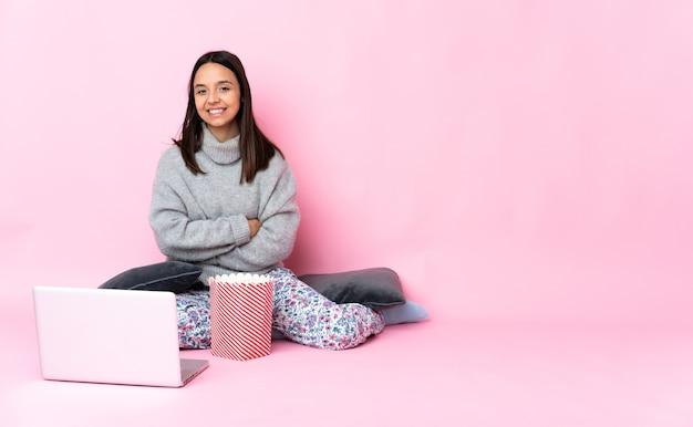 Jonge gemengde rasvrouw die popcorn eet tijdens het kijken naar een film op de laptop met gekruiste armen en vooruit kijkend